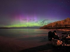"""Superior Auroras  Photograph by Shawn Malone    A burst of solar wind—charged particles from the sun—struck Earth on Tuesday, triggering auroras as far south as Michigan, as seen in this picture taken from the shores of Lake Superior in Marquette.    """"Just saw some amazing aurora this morning. Color was unreal. Haven't seen this kind of activity in awhile,"""" photographer Shawn Malone said in an email."""