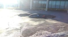 TORONTO PARKING LOT - A car that fell into a large sinkhole in the city's west end Wednesday morning is shown.  © Cam Woolley