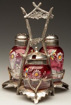 BARREL - ELLIPSE OVAL THREE-PIECE CONDIMENT SET, rubina with polychrome floral decoration, comprising a salt and pepper shaker with matching period two-part lids, and a mustard pot with a period lid. Fitted in a quadruple-plate stand, appears to be marked for Toronto Silver Plate Company. Fourth quarter 19th century.