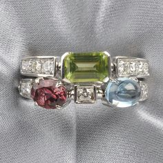"18kt White Gold Gem-set ""Color Collection"" Ring, Bulgari, set with various shaped gemstones including blue topaz, peridot, and rhodalite garnet, further set with full-cut diamond melee, size 7 1/2, signed"
