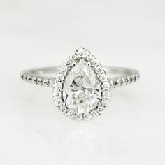 This pear shaped diamond 14K white gold engagement ring is both elegant and timeless. A halo frame lined with smaller round accent diamonds surrounds the 1.22 ct pear center stone, while additional ac