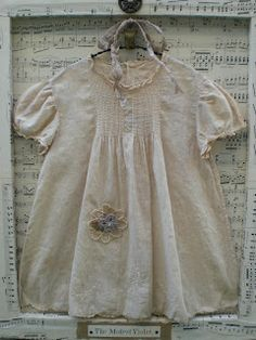 Display a baby dress on a canvass frame.