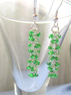 These silver and green earrings are made using the Shaggy Loops chainmaille technique. They measure at 1.75 inches (4.44 cm) from the top of the earring hook and dangle just over 1 inch (2.54 cm) from the bottom of the hook.   The beads are high quality Japanese Toho seed beeds in Grass Green, and the jump rings are silver plated copper. The earring hooks themselves are stamped .925 sterling silver.   $17.50