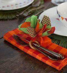 Um anel de madeira, daqueles de colocar a cortina, só precisa de um enfeite colorido para dar vida à mesa