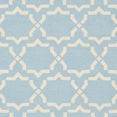 Moroccan inspired design and dense hand-woven wool pile highlight this handmade dhurrie rug. This floor rug has a light blue background and displays stunning panel colors of ivory.