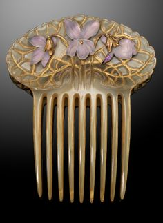 Vintage Art Nouveau haircomb by René Lalique, the horn comb applied with three foil backed frosted glass violets. Mounted in gold. Signed LALIQUE to reverse.