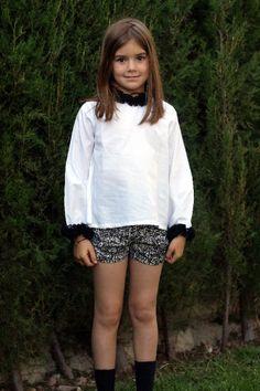 Blusa en popelin blanco adornada con volante de gasa negra en cuello y puños.