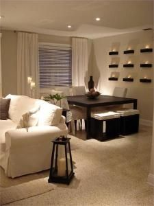 Basement living space. Love the candles on the wall and the warmth from the light couches and dark table. I can see family nights down here!