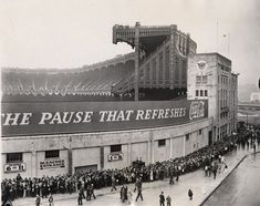 Yankee Stadium. Fans line up outside the left field bleachers to buy tickets to an important game – note the bunting draped over the upper deck.