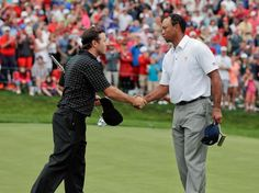 United States team player Tiger Woods, right, shakes hands with International team player Richard Sterne