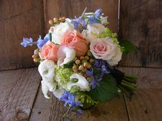 Bridesmaid bouquets - white miniature callas, peach Hypericum berries, 'Baby Green' hydrangea, light blue delphinium, white ranunculus, 'White Majolica' and 'Porcelina' spray roses, 'Sun Master' and 'Polar Star' roses.  The attendants wore pale peach dress, so we used Navy as the accent wrap on the stems.