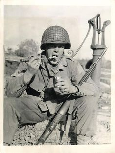 1944- U.S. soldier eats his rations with a paratrooper's knife in the Normandy beachhead sector of France.