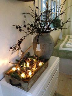 Holzkiste mit Tannenzapfen und Lichterkette