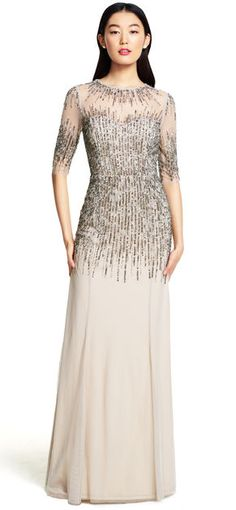 A stunning cluster of beads and sequins sprawl across the bodice and mesh sleeves of this floor-sweeping gown.