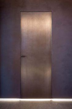 Porta e micromaniglia in ferro brunito, design studio Baciocchi Associati. La superficie cangiante dà luce all'interior. Fabbroni Serramenti