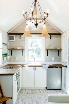 The bright interior walls and flooring contrast nicely with the warm wood accents and butcher block countertop.