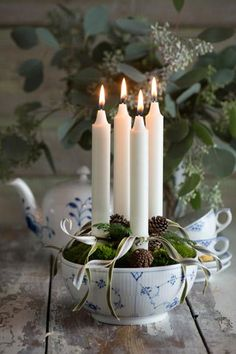 Advent candles in a bowl with greens, cones and ribbon