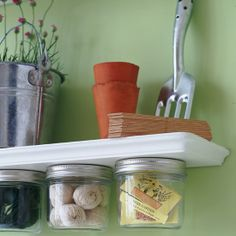 Little jars stuck under a shelf to create more storage for tiny things.