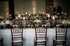 Long tables with candles, greenery & white flowers | Brookelyn Photography  http://www.storyboardwedding.com/chic-red-hook-brooklyn-liberty-warehouse-wedding/