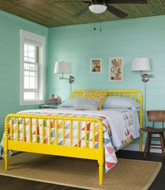 """Seafoam green and school bus yellow may sound over the top, but the duo actually works in this bedroom because the """"cool"""" wall color takes the edge off of the """"hot"""" bed frame shade. The quilt, which features both tones, bridges the gap. RELATED: 101 Bedroom Design Ideas"""