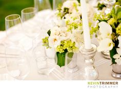 Wedding reception table setting and centerpiece flowers and candles. White and green theme. www.kevintrimmer.com