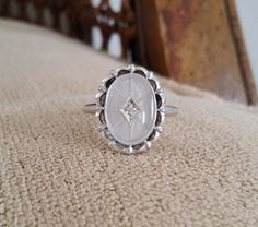 This Stunning Antique Ornate Ring features a 10K Antique White Setting. Also features a Marquise Etched Frosted Glass camphor set with a .01 carat