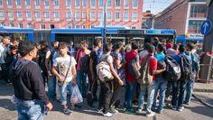 Flüchtlinge warten vor dem Münchner Hauptbahnhof darauf, in einen Shuttle-Bus einsteigen zu können.