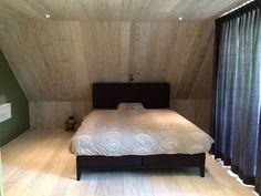 Slaapkamer waarvan plafond, vloer en schuine wand zijn afgewerkt met steigerhout in whitewash. Alles ontworpen ism opdrachtgever. Uitvoering door www.steigerhoutenzo.com