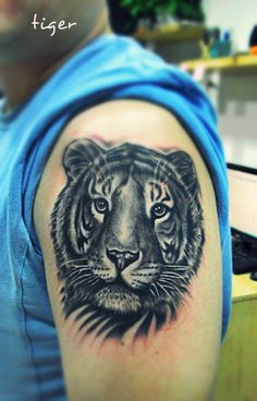 a tiger tattoo on the arm with vivid eyes
