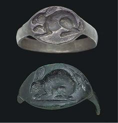 TWO GREEK FINGER RINGS CLASSICAL PERIOD, CIRCA 4TH CENTURY B.C. Including one of silver, with a plain flat hoop and an oval bezel, with a rabbit in profile to the left; and one of bronze, with a plain hoop, largely lost, and a pointed oval bezel, with a rabbit in profile to the left, the fur detailed by careful incising, on a groundline, a lizard in the field to the upper right