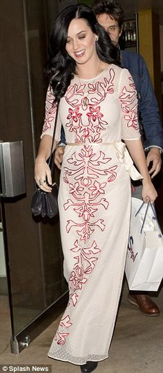 Vintage style: Katy Perry highlighted her tiny waist by wearing a cream ribbon around her middle, and accessorised with black shoes and purse, and gold jewellery