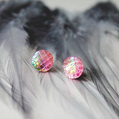 Beautiful pink iridescent dragon scale stud earrings. Silver plated material with a butterfly fastening. Look amazing in different lights. Earring diameter 12mm.