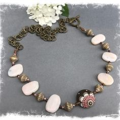 Raspberry Fields Design | Wearable Art Jewelry Golem Studios focal bead in pink, espresso, and latte, with rose quartz stones and Czech glass bicone beads.