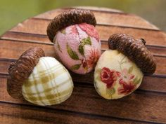 acorns, these look like the have deco glued on fabrics, but they might be painted.  Would be cute hung from a Christmas tree if Christmas fabrics were used.