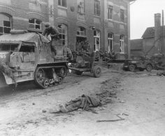 US soldiers of the 16th Regiment, 1st Infantry Division rest outside a building in the German town of Vettvays. Passing through is an armored half track towing a 57mm antitank gun. In the foreground lies a German KIA; Feb 28, 1945.