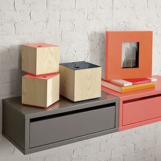 Wall mounted storage shelf. ($129.00). Smart option for small space lodgings. Peach lacquered modular nightstand floats a flip-down door to keep floor space open.