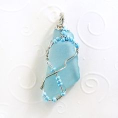 "Pretty translucent, light blue cultured sea glass wrapped in silver plated jewelry wire and accented with pearly blue seed beads. 1.75"" x .75"" (4cm x 2cm) Your handmade sea glass pendant will arrive o"