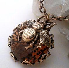 This Statement Bee necklace is an updated version of my best selling Queen Honey Bee jewelry design. This stunning pendant necklace displays an enchanting queen honey bee set on a large and rare honey topaz Czechoslovakian glass jewel. The glass stone is encased in a hand made filigree setting that can be seen through the stone for a magical effect! Necklace size is adjustable for a perfect fit, choose your necklace length upon checkout. Pendant 1 5/8 L x 1.25  W (4.12 cm L x 3.17 cm W)…