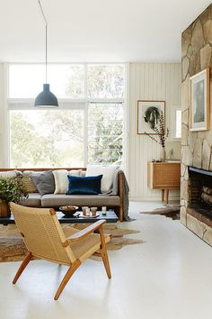STYLIST'S BLUE BEACH HOUSE IN SYDNEY -  overall colour palette is pared back and dominated by white, blonde wood and earthy tones with a few navy accents. Even the artwork of mostly black and white photography blends in with the owners collection of vintage Danish furniture and makes this home feel calm and peaceful.