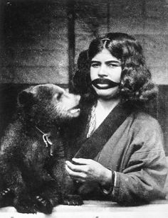 """Juliet Bredon photographed this tattooed Ainu woman with her bear in 1922. She published the photograph in National Geographic under the pseudonym """"Adam Warwick,"""" likely in an effort to escape discrimination based on her gender."""
