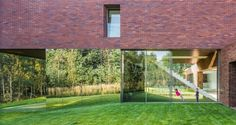 Stainless steel mirror walls and a transparent interior with a grass floor make the lower floor virtually invisible.