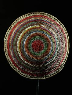 Africa | Imbenge Beer Pot Lid | Zulu peoples, South Africa | Traditionally these pot covers, were woven from grass fibers. More elaborate beaded versions, were treasured articles and are only brought out when guests were being entertained. | This example is made from colourful telephone wire.