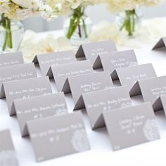 "Simple DIY name cards. The escort cards were an easy DIY project. ""We used place cards in gravel from Paper Source,"" explains Jen. ""We stamped a flower in white in one corner of the card, and names were written with a white gel pen."""