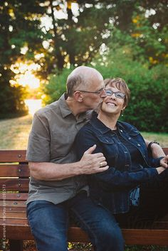 Middle aged, retired couple kissing and cuddling outside sitting on a bench by robcampbell | Stocksy United