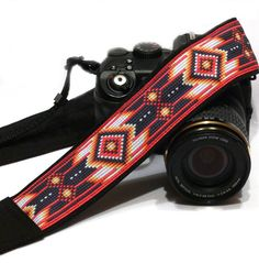 Black and Red Native American Inspired Camera Strap. More camera straps here https://www.etsy.com/shop/LiVeCameraStraps?section_id=16781873 Beautiful, stylish camera strap for dSLR / SLR body style cameras with focus on durability, strength and comfort. Adjustable features for preferred positioning either around your neck or across your body Measurements: Total length - 60 inches / 152 cm Fabric length - 30 inches / 76 cm Adjustable webbing length (each) - 15 inches / 38 cm Width of fa...