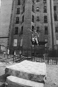 1970s New York:  A boy jumps off a jungle gym on to a mattress in a vacant lot by an abandoned building on the Lower East Side.  (Photo by Allan Tannenbaum)