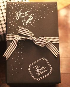 Simple holiday gift wrapping. Black Kraft wrapping paper decorated with white marker.