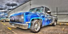 Custom painted silver with blue flames American pickup truck on display at a car and bike show in Melbourne, Australia.