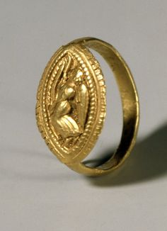 Graeco-Etruscan. Pale gold finger-ring; pointed oval bezel with design in relief: Nike flying to left, holding a taenia; stippled background.