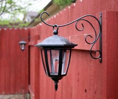 Solar lights hung on plant hangers for your fence. Great idea!